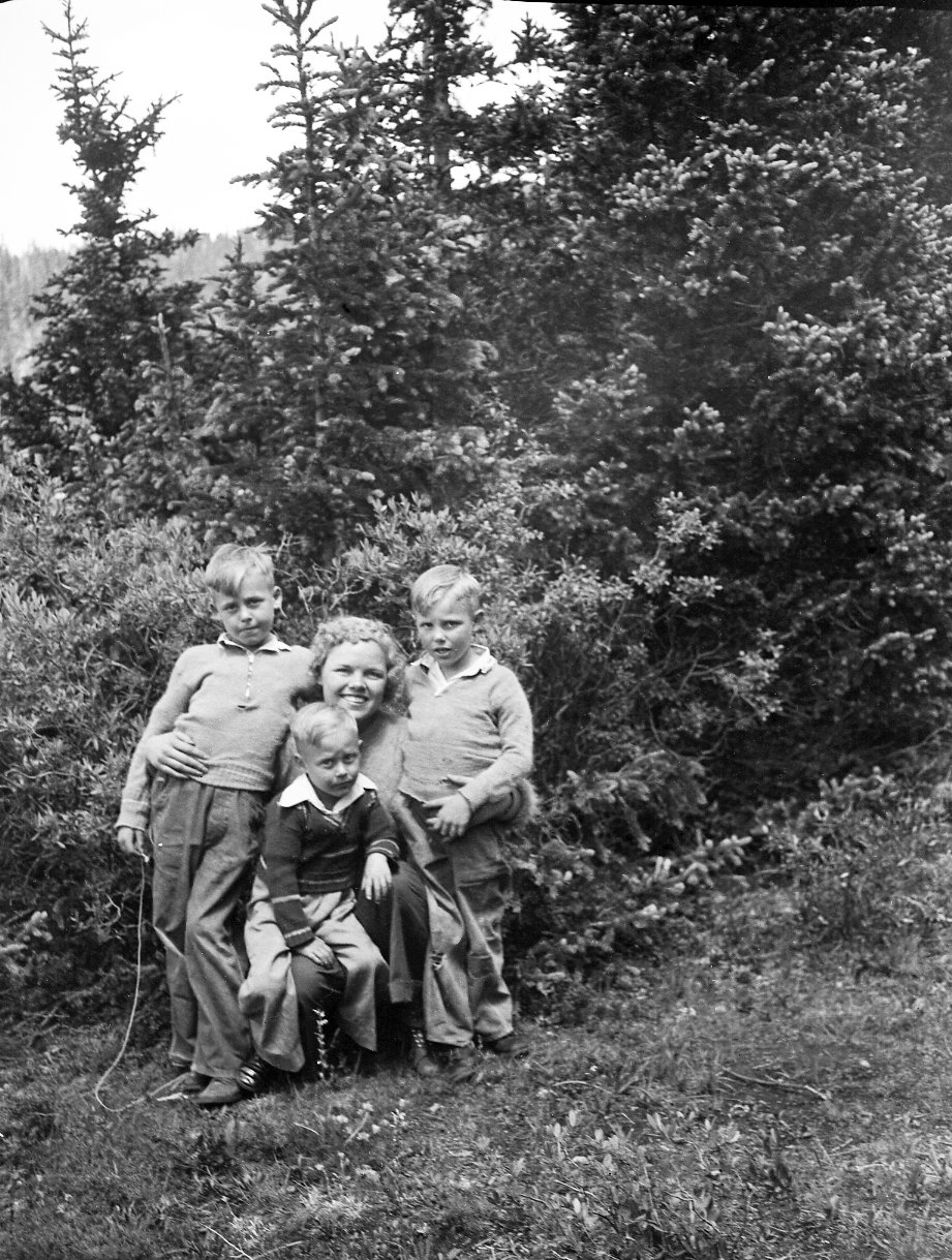 Three boys pose with an unidentified woman in the mountains.