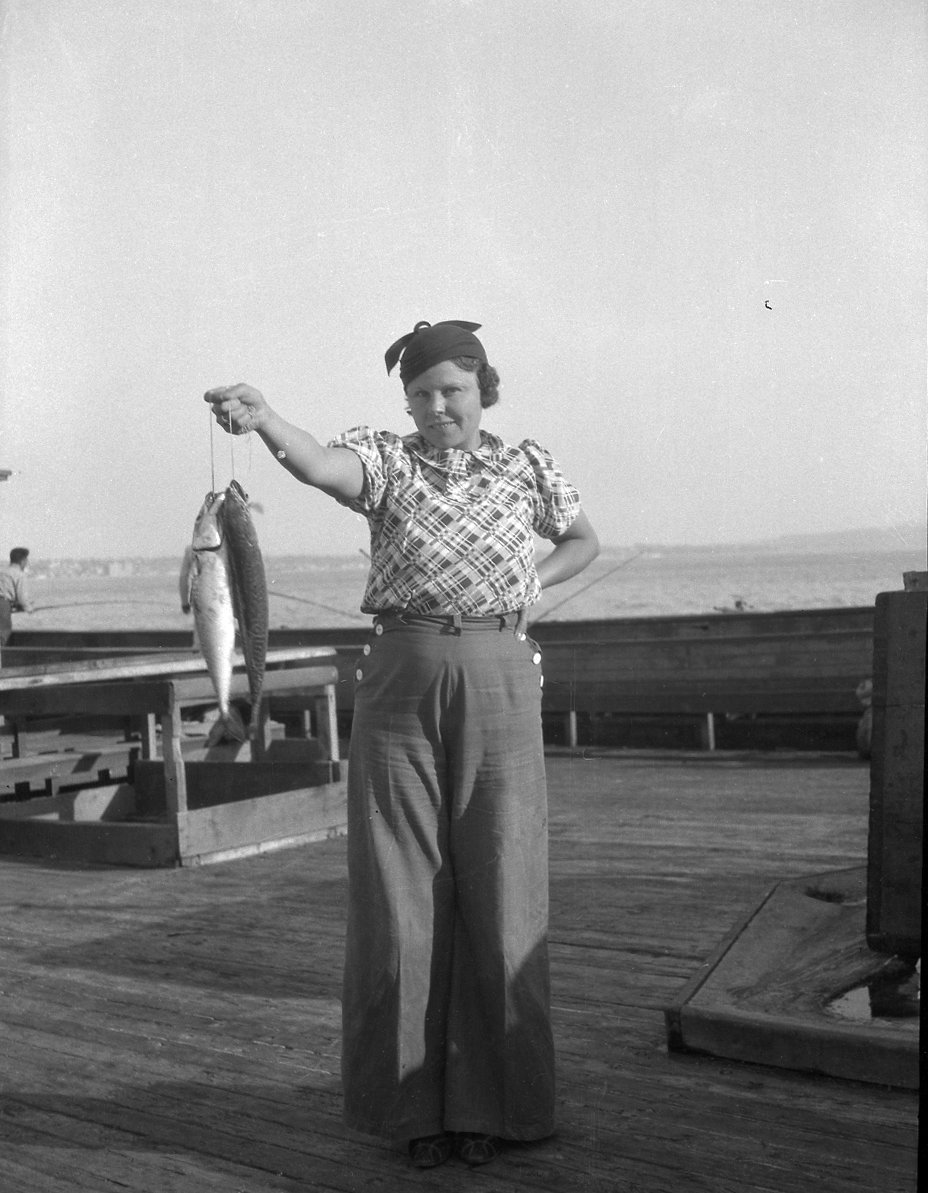Young woman holds two fish recently caught.