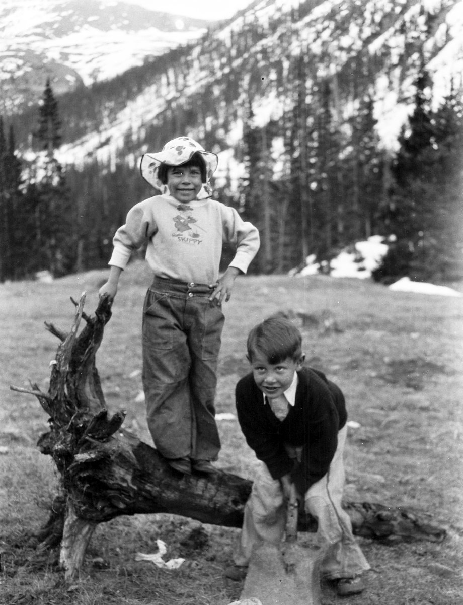 Boy and a girl pose by a burned out tree stump.