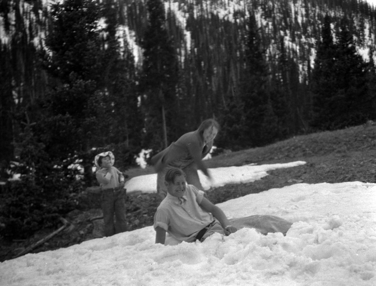 Robert Landberg and friend play in the snow while young girl looks on.