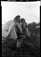 Eskimo man holding a baby in Wainwright, Alaska