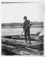 Man aboard a log raft