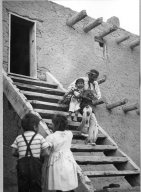 San Ildefonso Pueblo, Corn Dance. War Captain (?) carring youngest participant down steps, two young children watching from bottom