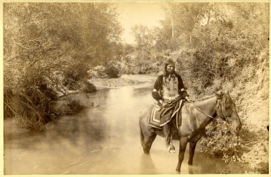 Indian male on horse in stream