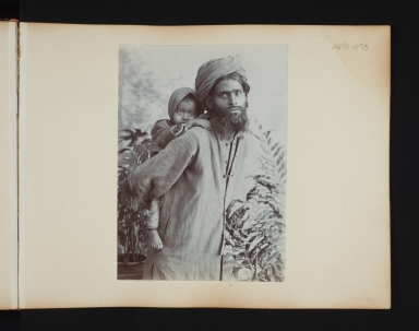 Bearded man in turban with a child on his back in Simla, India.