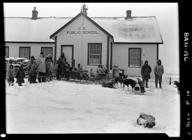 Eskimos and sled dogs in front of a school house
