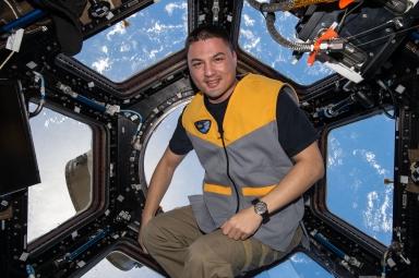 Kjell Lindgren sitting in front of the International Space Station