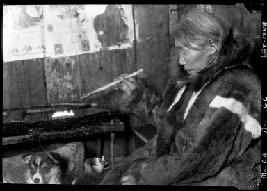 Eskimo woman with a sealoil lamp