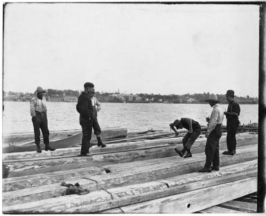 Men aboard a log raft