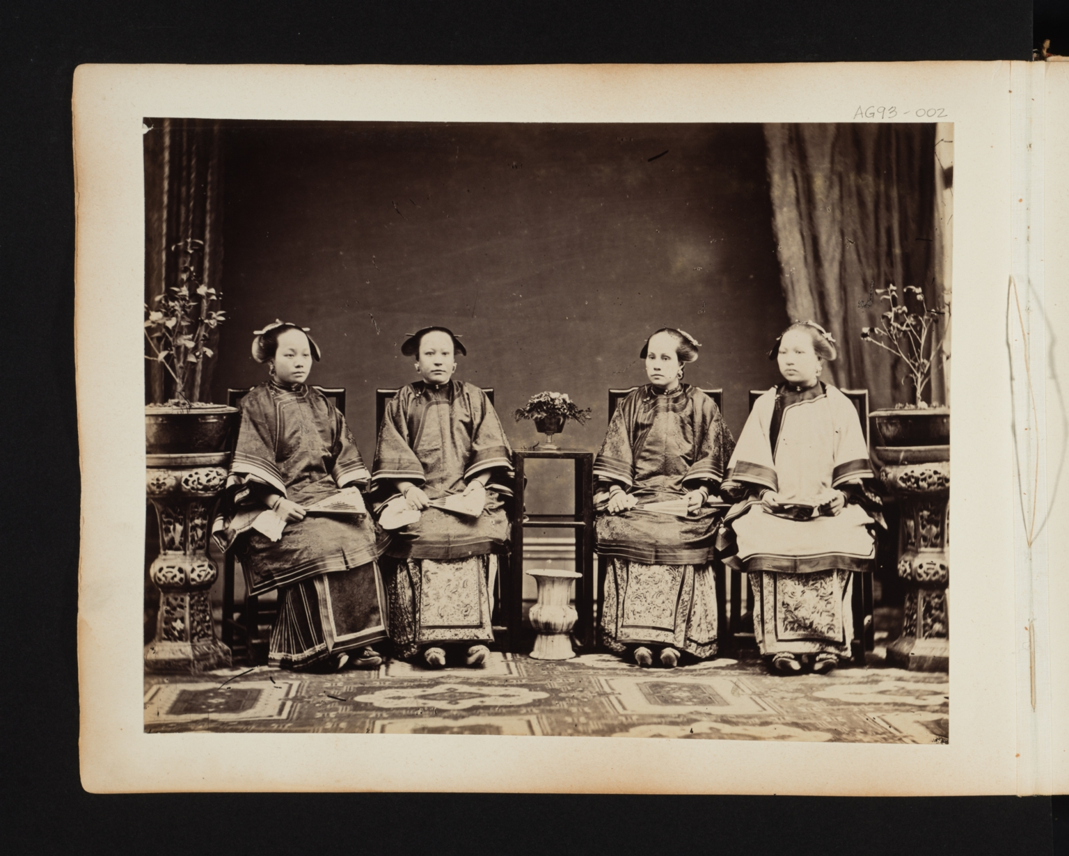 Four seated oriental women with fans.