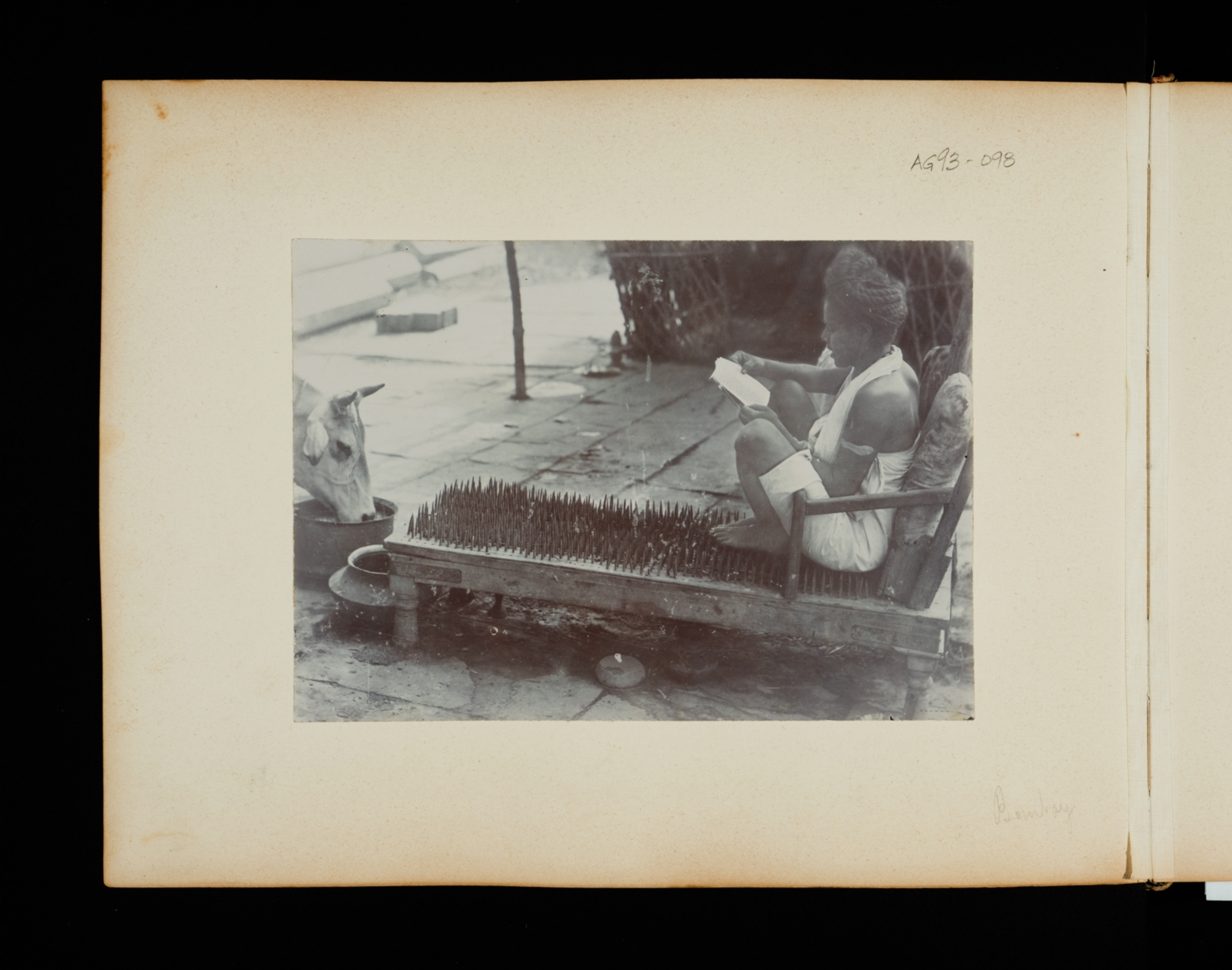 Fakir sitting on a bed of nails in Bombay, India.