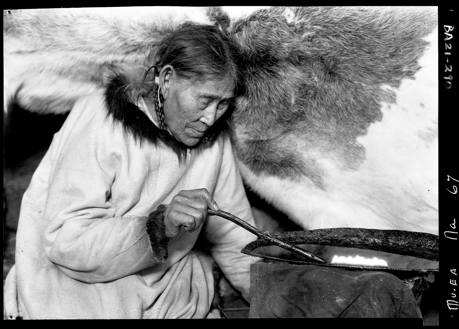 Eskimo woman with a seal oil lamp