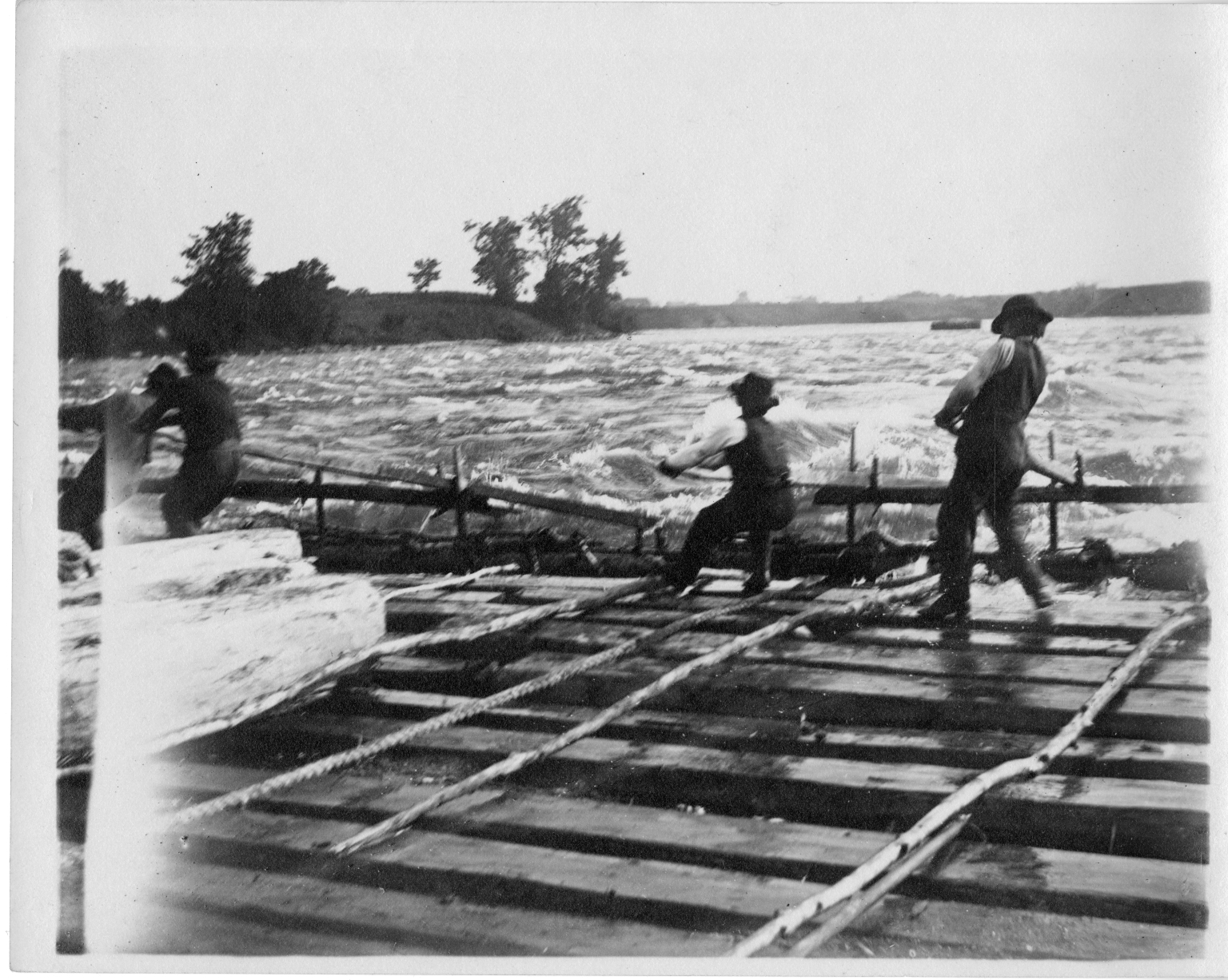 Men manuvering a log raft