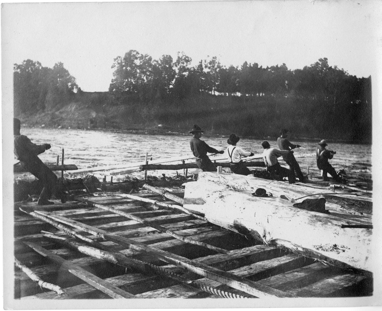 Men manuvering a log raft