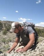 Dr. Joseph Sertich, DMNS Curator of Vertebrate Paleontology, carefully examines a new specimen.