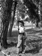Boy holds a pistol and a rifle while wearing a hat.