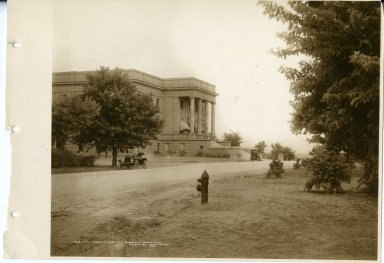 View of Denver Museum of Nature & Science 1908 building with cars and fire hydrant in the foreground.