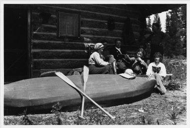 Unidentified people outside log cabin