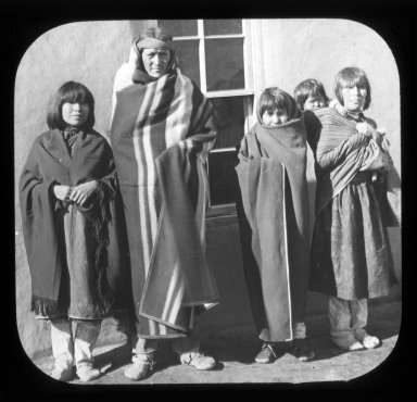 Native Americans standing in front of a wall.