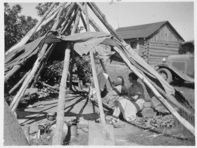 Anglo nurse, Miss Hunter and Jicarilla Apache women seated inside tipi pole framework
