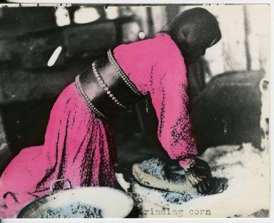 Apache woman grinding corn on metate