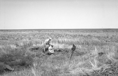 Clyde Fisher and unidentified woman examining crater