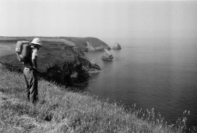 Fran Hall standing on a cliff overlooking water.