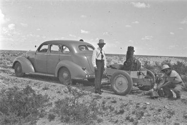 H.H. Nininger and unidentified man next to automobile pulling magnetic rake and metal detector