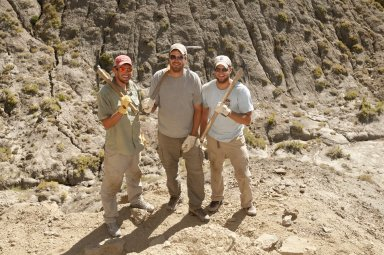 L-R: Dane Miller, Dr. Ian Miller, and David Allen shoulder their picks as they pose at a dig site on the Kaiparowits Plateau.