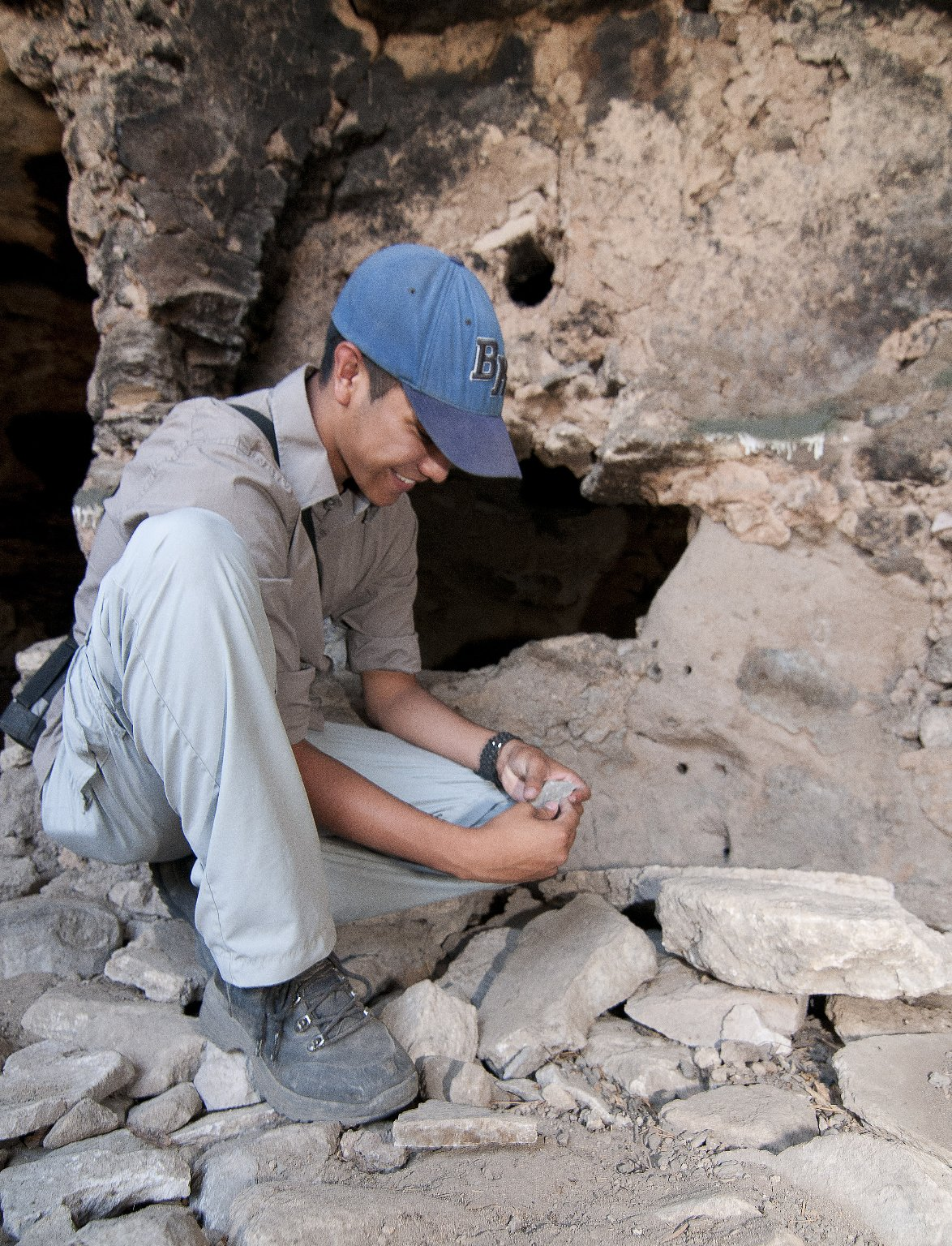 Vincent Morris examines an object at the Hinkle Park Cliff Dwelling research site.