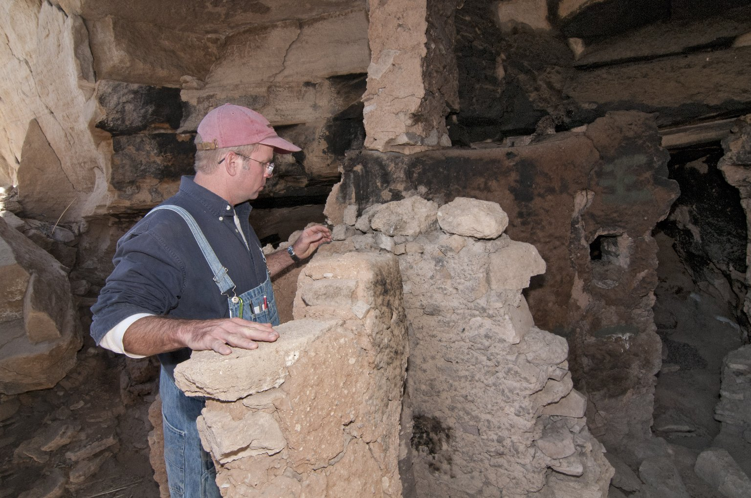 Dr.Steve Nash looks at the top of a wall at the Hinkle Park Cliff Dwelling.