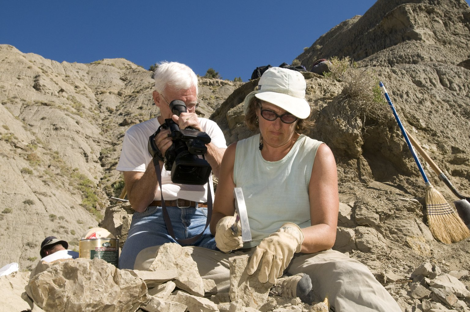 Dave Baysinger (left) films a DMNS Volunteer using a rock hammer to break open rocks to look for leaf specimens on the Kaiparowits Plateau.