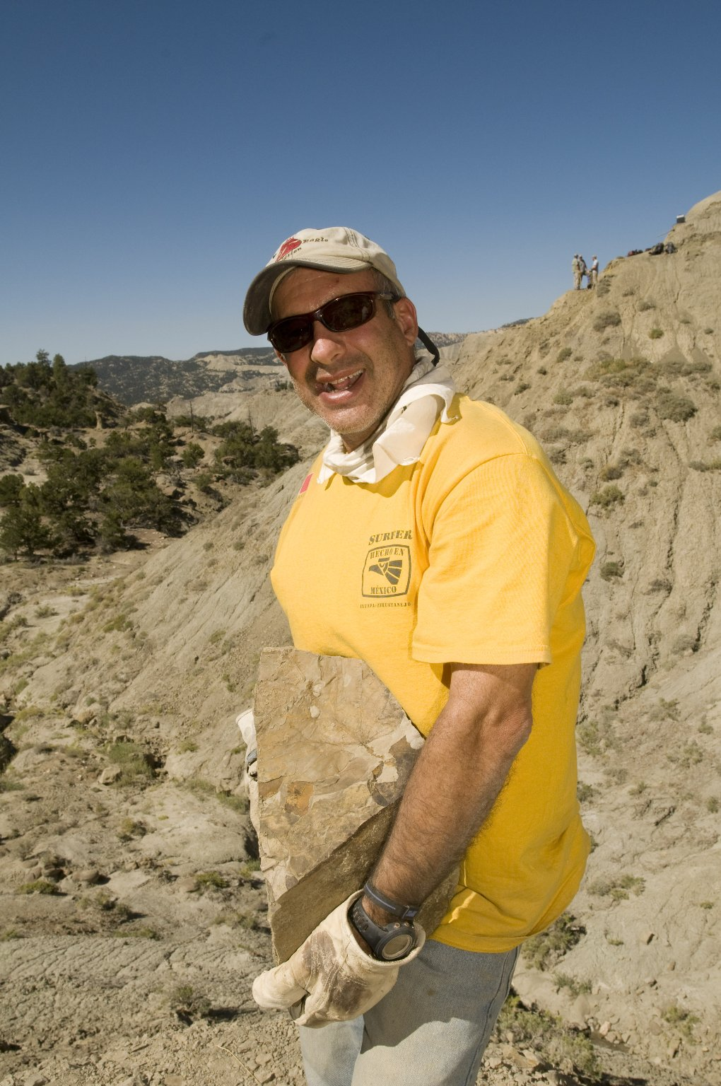 An unidentified DMNS Volunteer carries a rock with leaf specimens on the Kaiparowits Plateau.