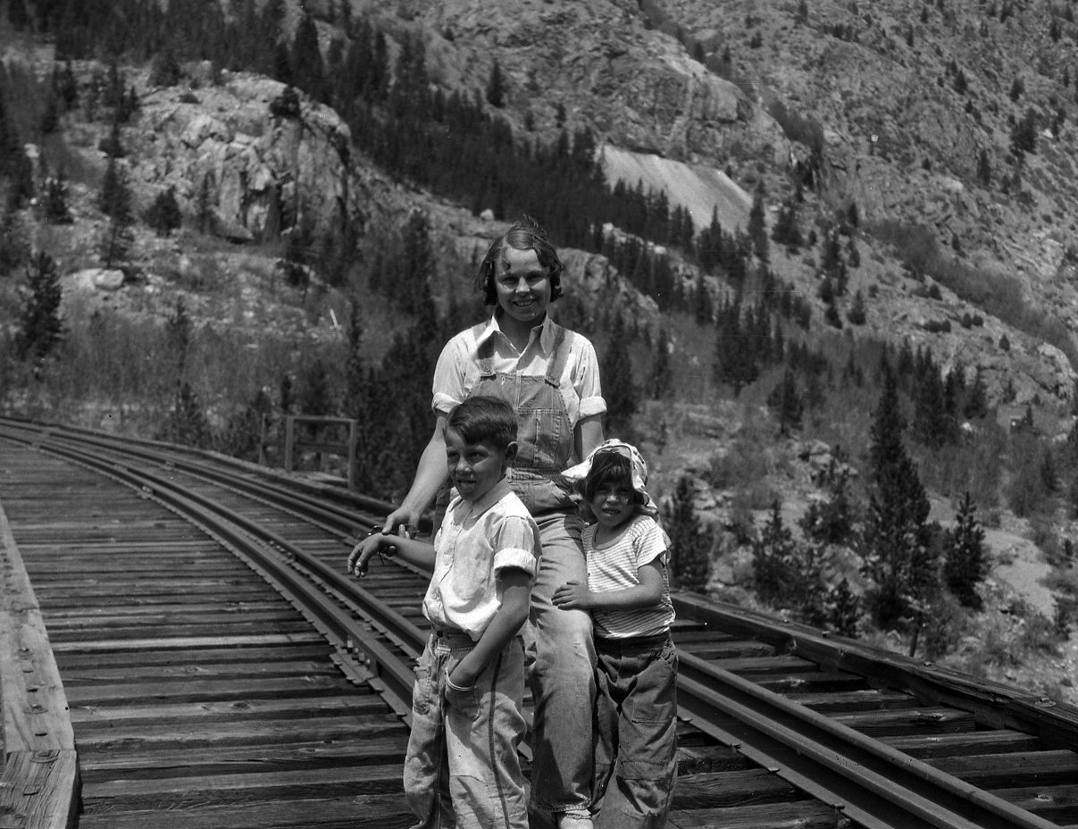 Woman and two children pose on a railroad trestle.