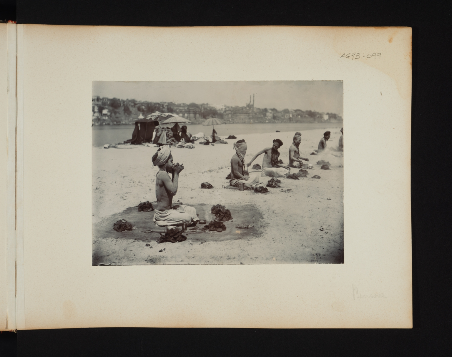Five seated Fakirs surrounded by small fires in Benares, India.