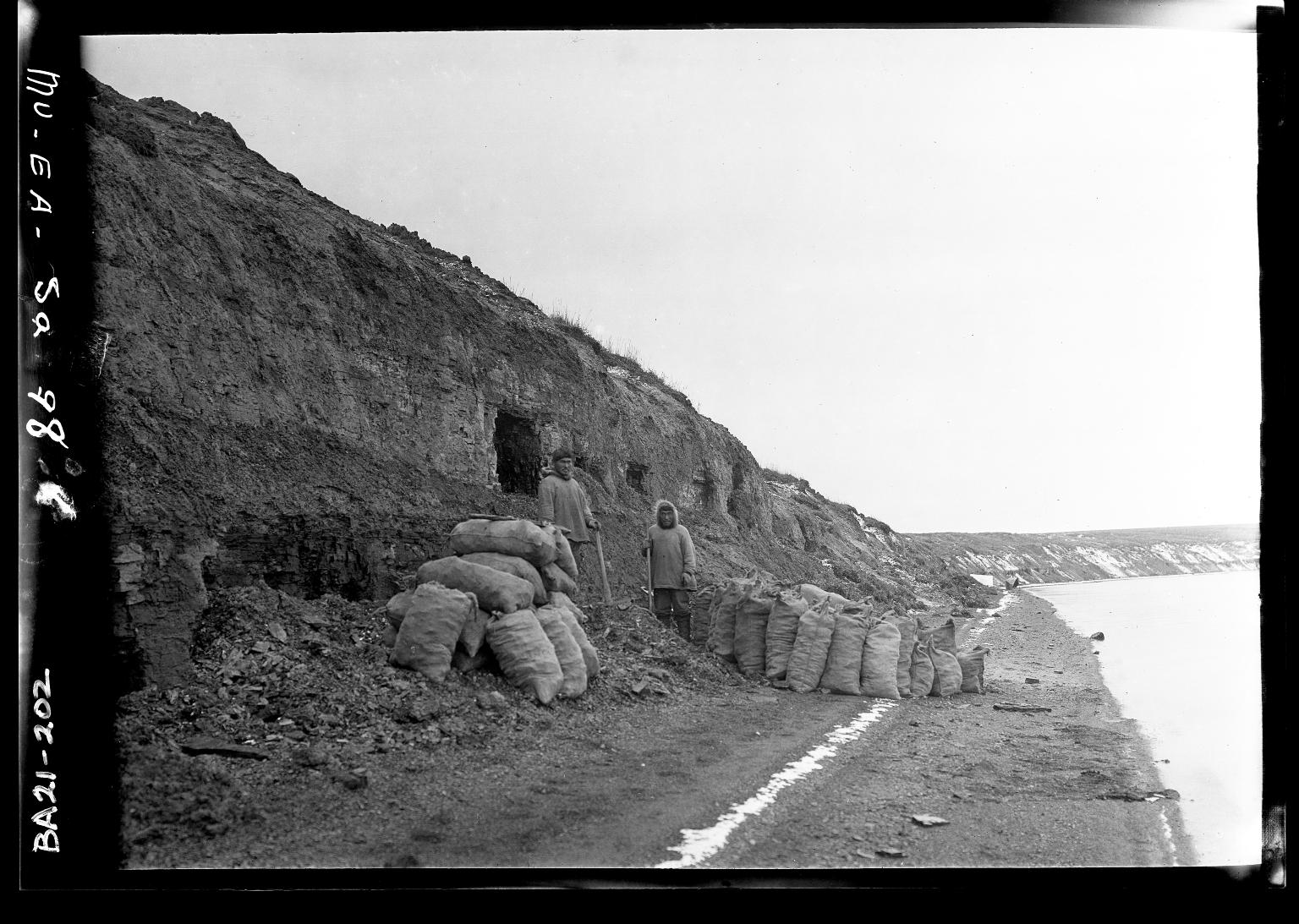 Eskimo men standing near the northern most coal mine in North America